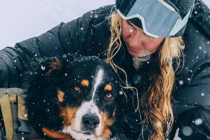 a blonde women wearing a black down jacket, black beanie with black and white ski goggles on her forehead, black snow pants and brown gloves holding her black, brown and white dog wearing a pack as he looks at the camera