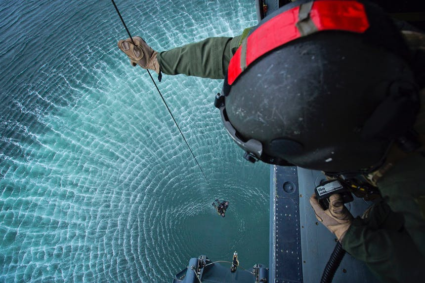 a photo from an Air Force helicopter looking down from behind a man holding a rappel line from the helicopter as another drops down for a water rescue below