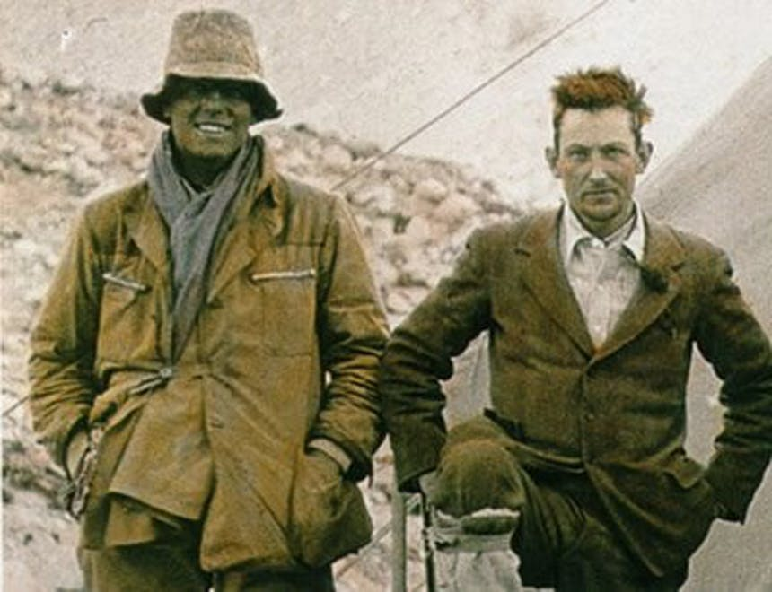 a historic sepia colored image of two men standing side by side, one dressed in a yellow jacket, grey scarf and bucket hat while the other is in a suit wearing a white shirt a tie