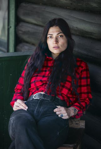 Native American woman leaning back in her chair on the porch of a wooden cabin wearing a black and red flannel shirt tucked into her black jeans and a black leather belt