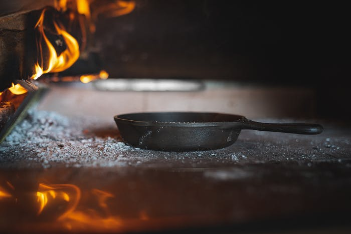 a black sand casted cast iron pan inside an out wood burning oven with wood burning on the left side of the outdoor oven