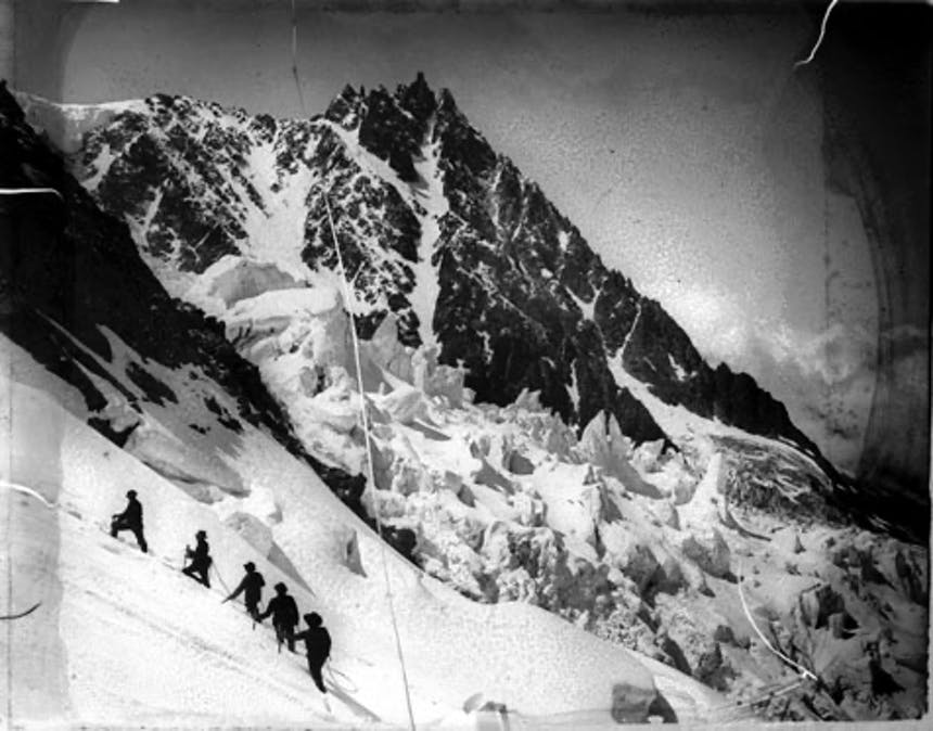a black and white image of a mountain peak close in distance while five people climb the steep incline from afar making them look like ants