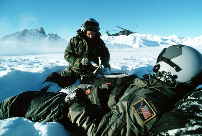 two Air Force men wearing green snowsuits, one sitting up, while the other lays down resting on a bag as a helicopter takes off in the snowy mountains in Alaska