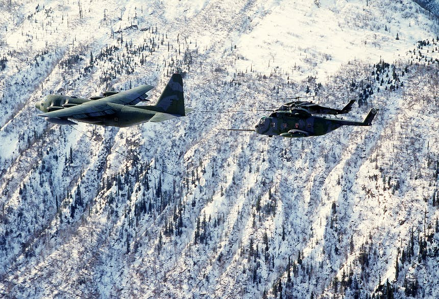 an areal view of two fighter jets flying over a very snowy Alaskan forest