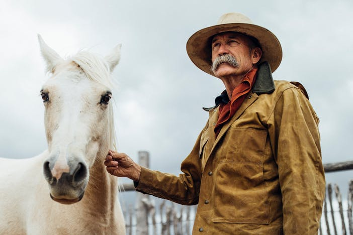 a white horse looking directly at the camera with an older man with a grey handlebar mustache, brown snap jacket, dark pants and red undershirt with his hand brushing the horses neck as they stand in a coral