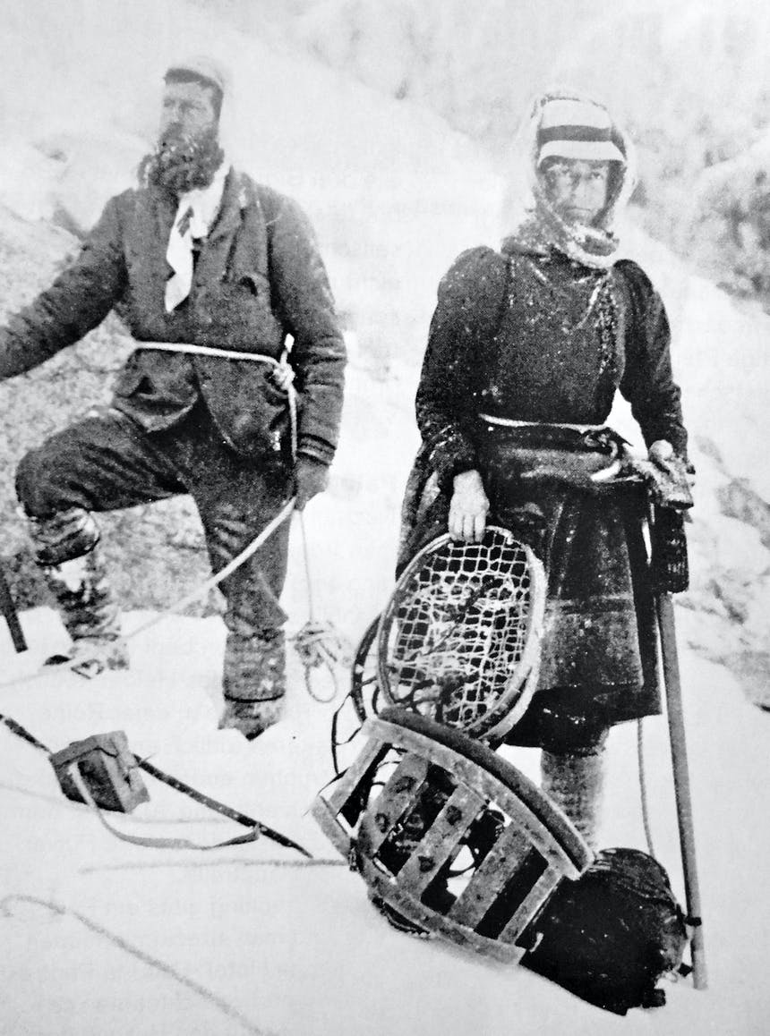 a black and white image of two mountaineers, one woman and one man, wearing thick jackets, trousers, boots and hats holding their snowshoes