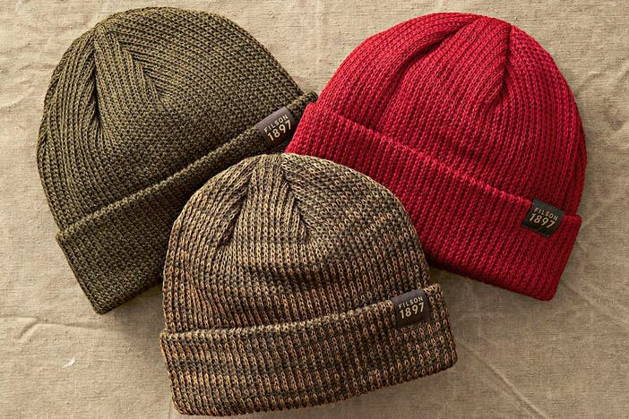 three beanies with the brim folded up, olive, green and red with a small FILSON 1897 logo on the right where the brim is folded