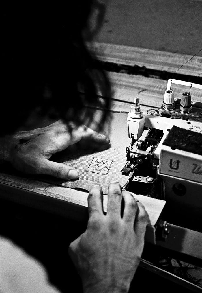an archival black and white image from behind the sewer working on sewing two pieces of fabric together on an old sewing machine with the original Filson logo already sewn on the bottom right corner.