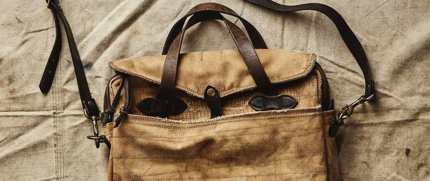 a top down view of a worn tan briefcase with leather handles and strap and extra stitching where it needed to be mended on a canvas backdrop