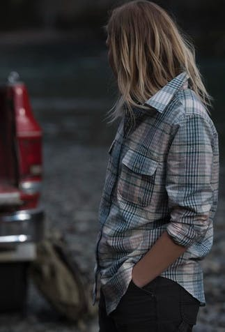 woman with dirty blonde hair wearing a blue, pink, and white flannel with the sleeves rolled up turned looking towards the bed of a red pickup truck where there is a silver box and two green duffle bags in the bed of the truck