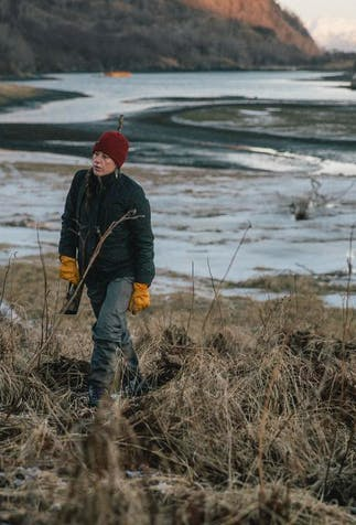 caucasian blonde woman walking away from a snow dusked grassy river bank wearing a red beanie, green jacket, yellow leather gloves and grey pants carrying a gun slung over shoulder
