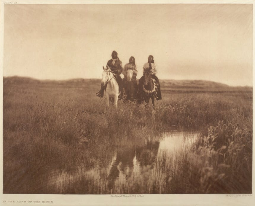 an old sepia colored image of three Native American Indian men sitting atop horses next to a creek all wearing traditional attire and long dark hair