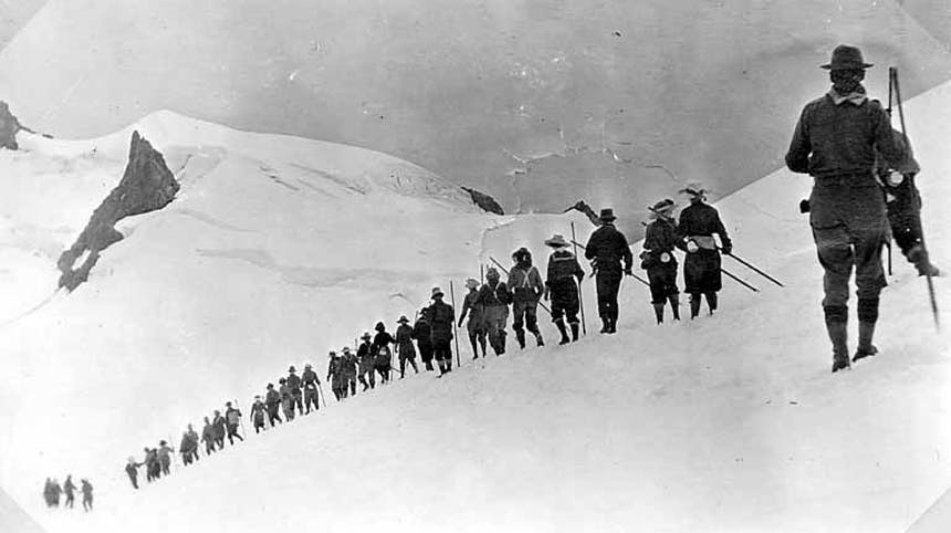 a black and white image of a long line of mountaineering men from behind as they traverse the rolling hills along a mountain ridge