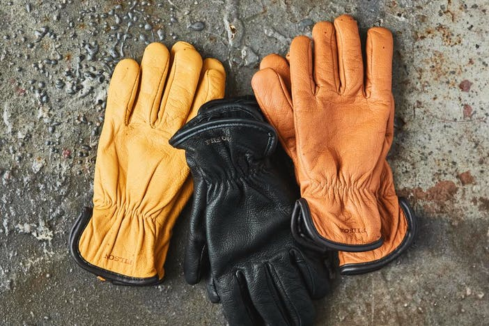 three pairs of goatskin gloves, yellow, tan and black laying on a concrete floor of a shop