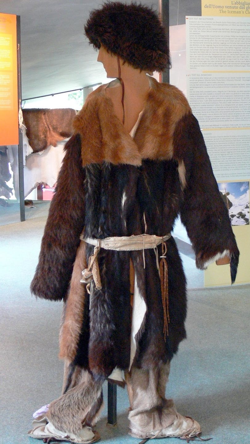 a museum reconstruction of an indigenous man wearing animal skins and furs of various brown colors