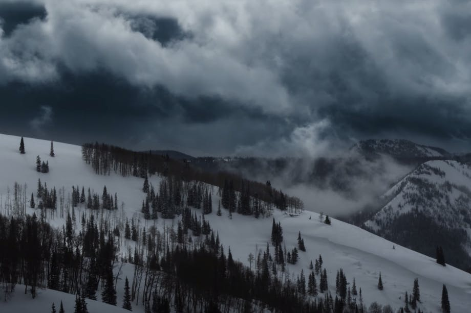 a snowy dark landscape of the Utah mountains with patches of trees and a storm rolls in