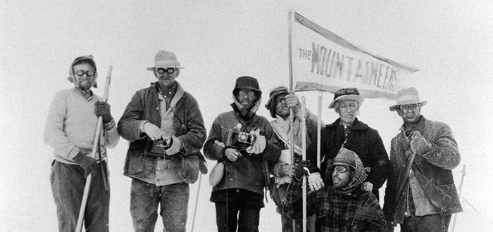 a black and white image of six men wearing a variety of jackets, hats and pants holding a flag reading the mountaineers