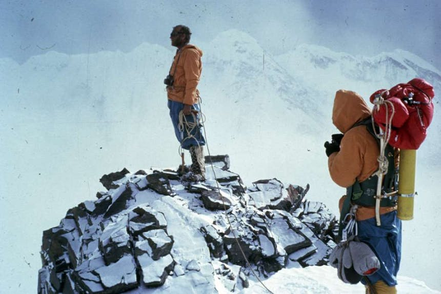 two men wearing orange insulated jackets, snow pants and insulated boots, one standing out on the rocky edge of a cliff, while the other take a photo while wearing a hiking pack that's yellow and red