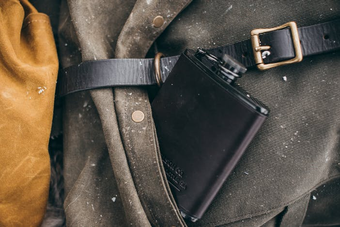 a close up shot of a brown leather metal flask tucked into a side pocket of a tattered rucksack