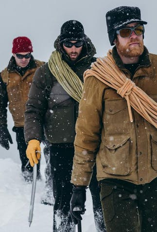 three men wearing thick coats, winter hats an carrying mountaineering gear, rope and tools, hiking along looking ahead