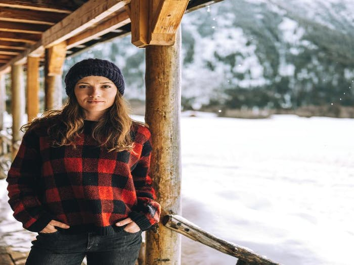 brunette woman standing on the porch of a cabin during a snowy winter wearing a red buffalo plaid sweater and hand knit beanie