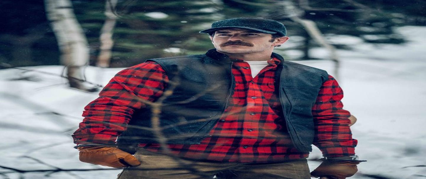 man with mustache wearing a red and black plaid flannel, grey vest, grey cap and tan gloves standing on a trail in the woods