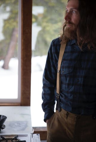 long hair and bearded man wearing a blue and black flannel with suspenders looking out a window in a cabin