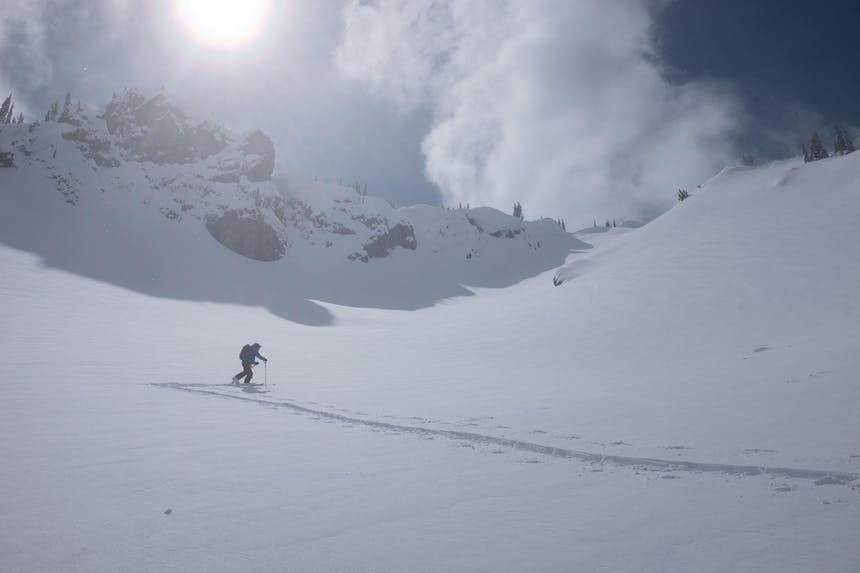 skier skiing up an incline to the top of a peak with the sun shining down
