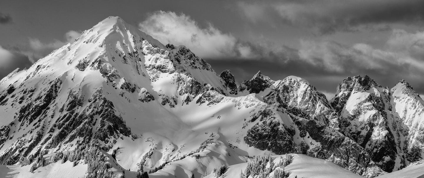 a black and white image of a snowy mountain peak landscape