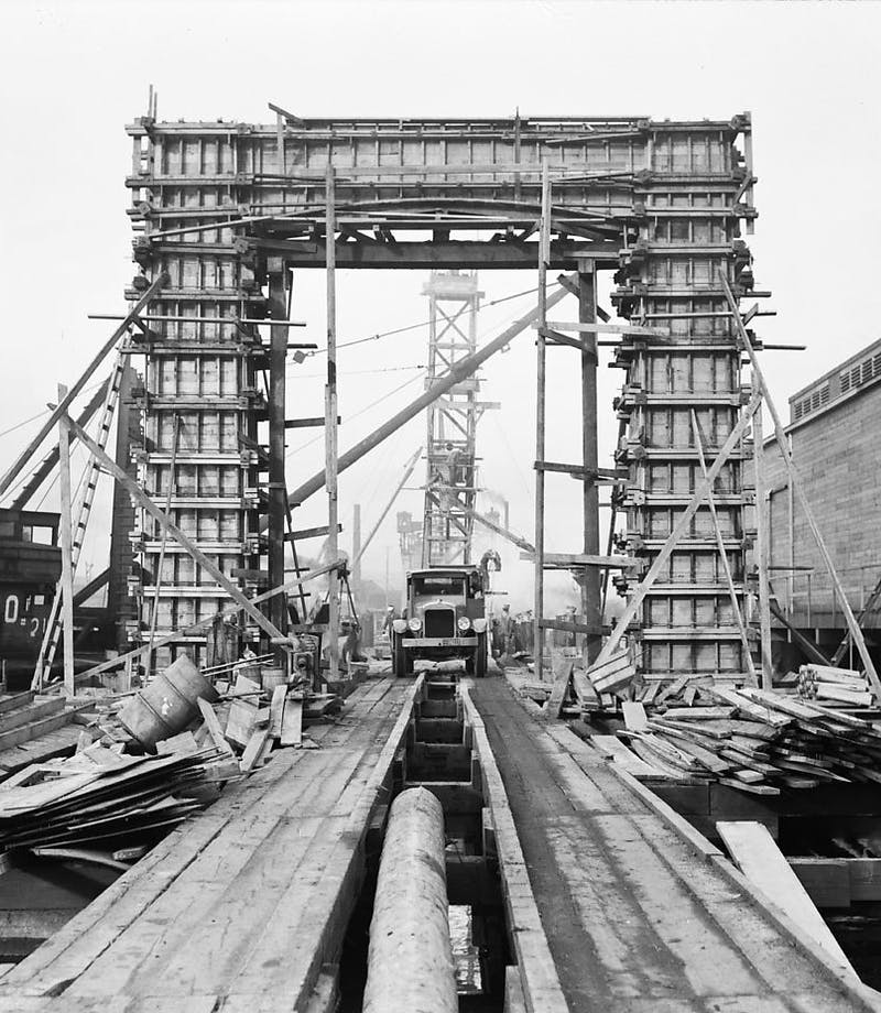 a straight on view of the work in progress build of the ballard bridge as an old car drives towards the cameraman