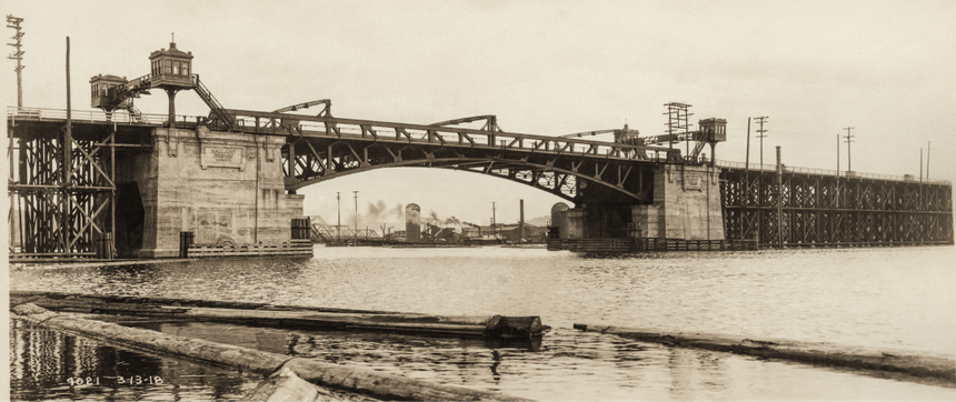 an old sepia colored image from the river bank looking up towards the ballard bridge build