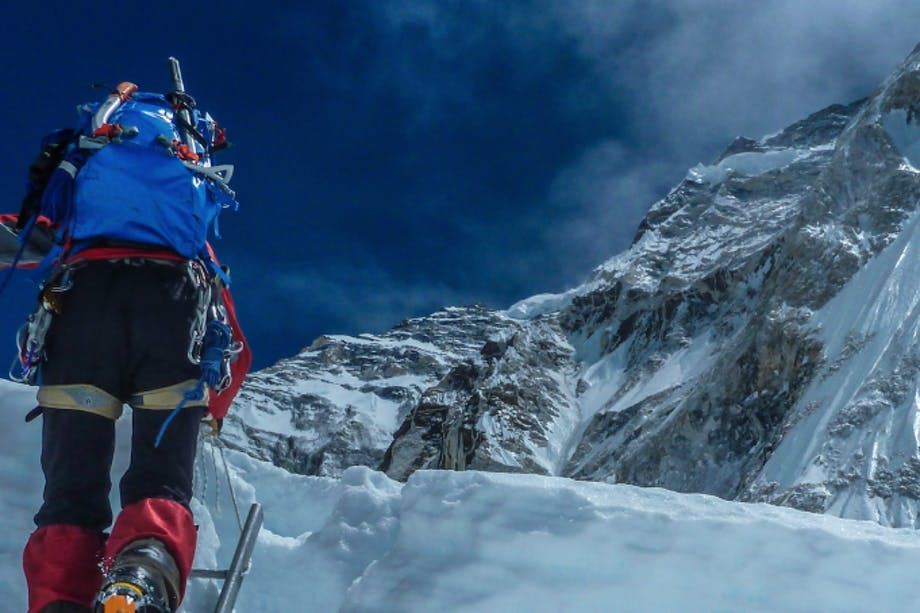 a view from behind a mounaineer scaling a large mound of ice with a metal ladder wearing black and red snow gear and a blue backpack