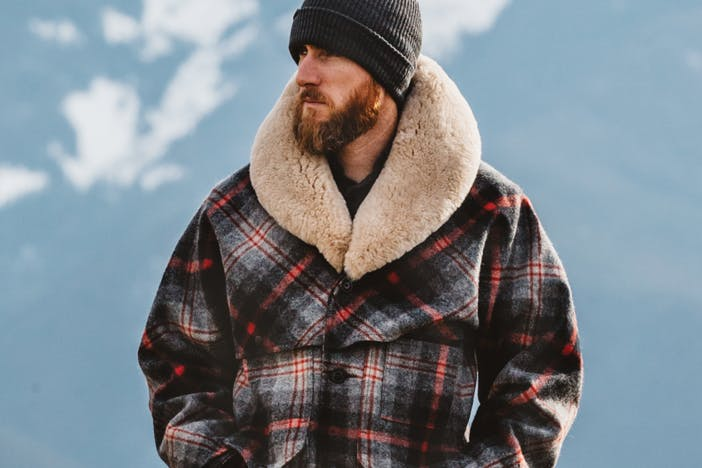 a bearded man wearing a grey beanie and a red, black and white plaid coat with a wool collar looking off to the left