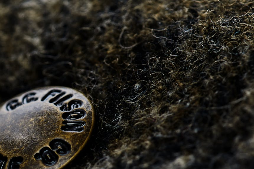 a close up image of a Filson wool coat with the bronze button reading Filson Co