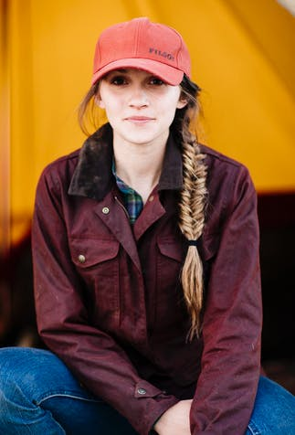 a brunette girl with a fishtail braid sitting in front of a orange backdrop wearing a burnt orange hat, dark red coat and blue jeans