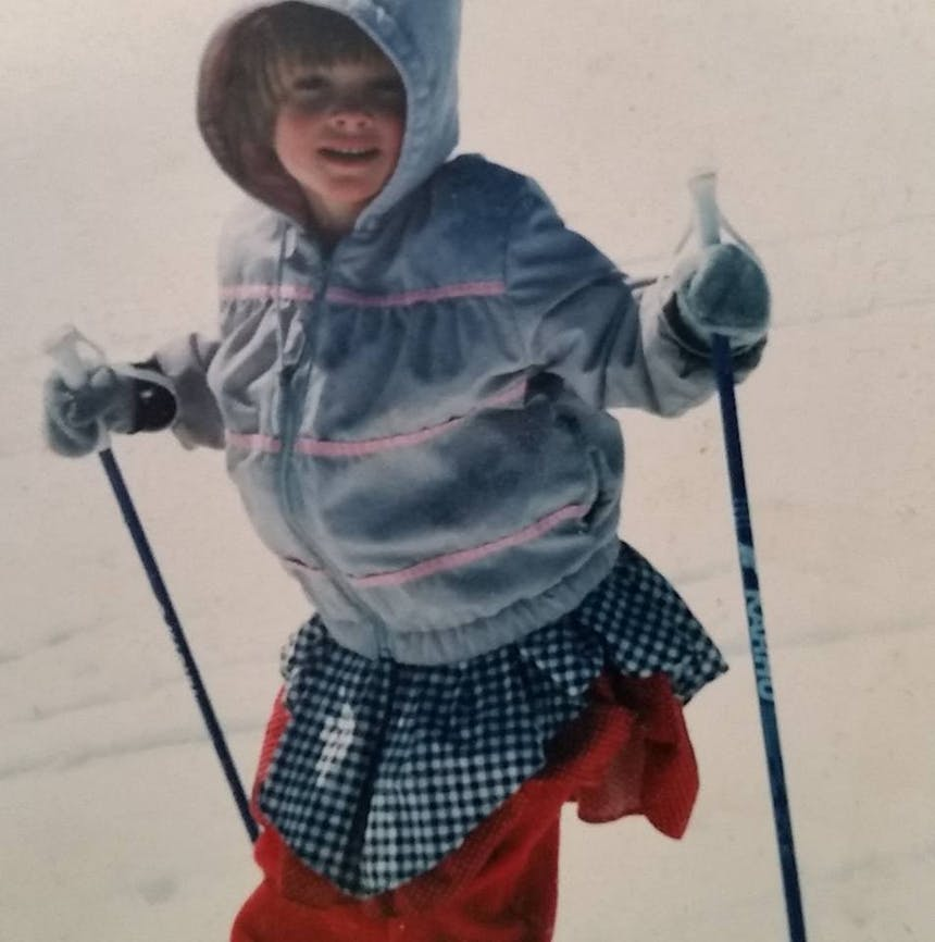 old film photo of a little girl wearing a colorful - blue, red and blue and white plaid - outfit skiing down a hill