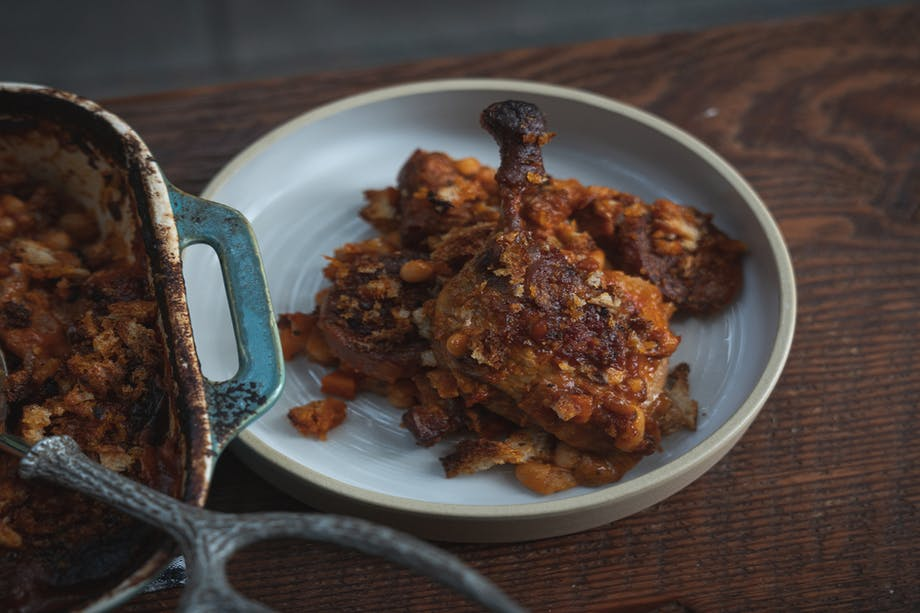 a close up shot of a plated duck leg with the fixings on a dark brown cutting board next to the blue and white ceramic cooking pan with a metal spoon for ladling
