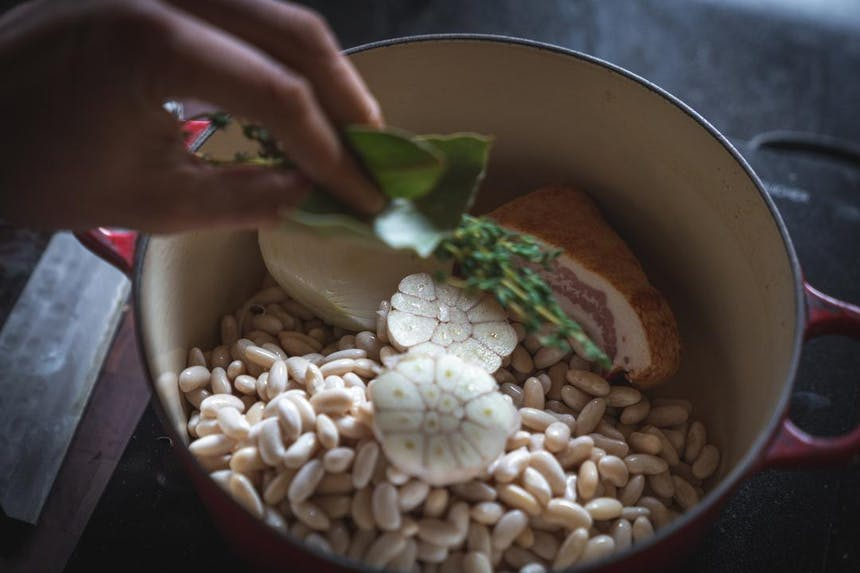 a top down view of a red and cream ceramic pot filled with white beans, a head of garlic cut in half, a slab of bacon and the chef tossing in a few sprigs of thyme and bay leaves
