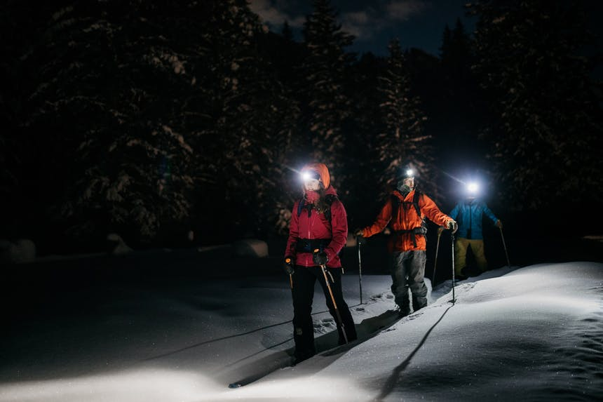 a night shot of a few people cross country skiing with headlamps on