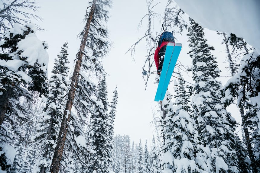 Skier off a jump in the trees.