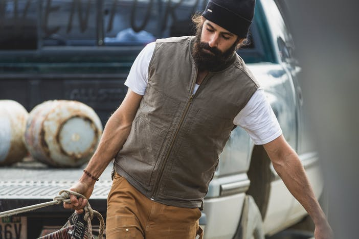 a dark hair and bearded man wearing a white t-shirt, brown vest, black beanie and tan pants leading to the right as he carries a net full of gear walking away from a truck with the tailgate down
