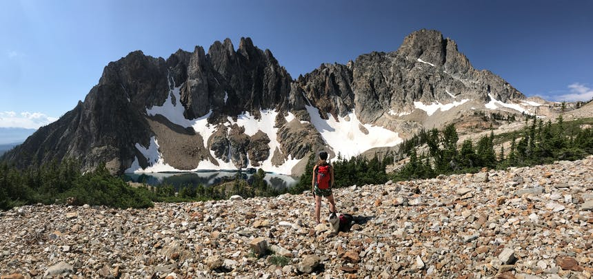 a landscape shot of jagged mountain peaks in the background of a girl standing on rocks for the photo