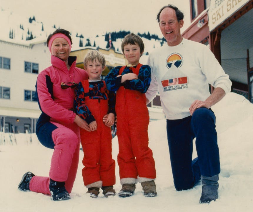 an old film photo from a family ski trip, mom and dad on either side of the two kids in the middle wearing red, blue and pink snow gear