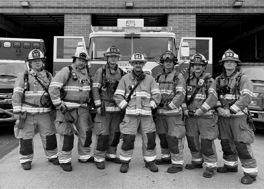 a black and white image of a fire crew wearing their gear standing in front of their truck outside their firehall