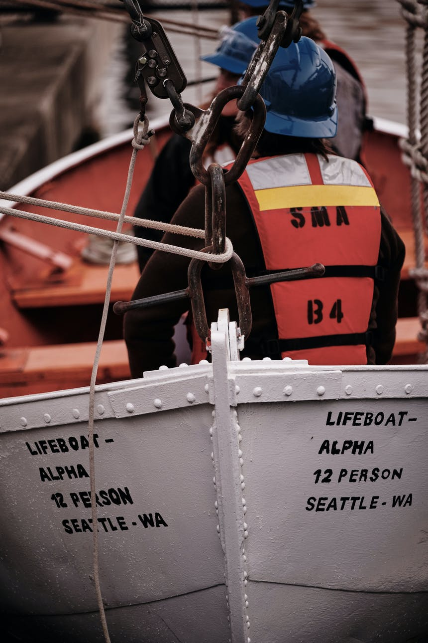 two Seattle Maritime Academy candidates wearing blue hardhats, orange personal floatation devices sitting in a white safety boat with orange pain on the interior