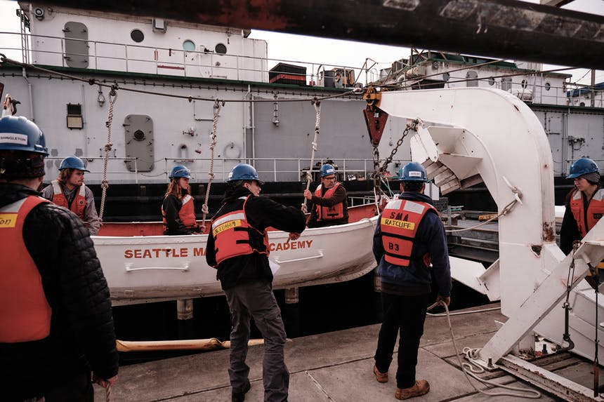 a view from behind six seattle maritime candidates working together to get the white safety boat back on the dock