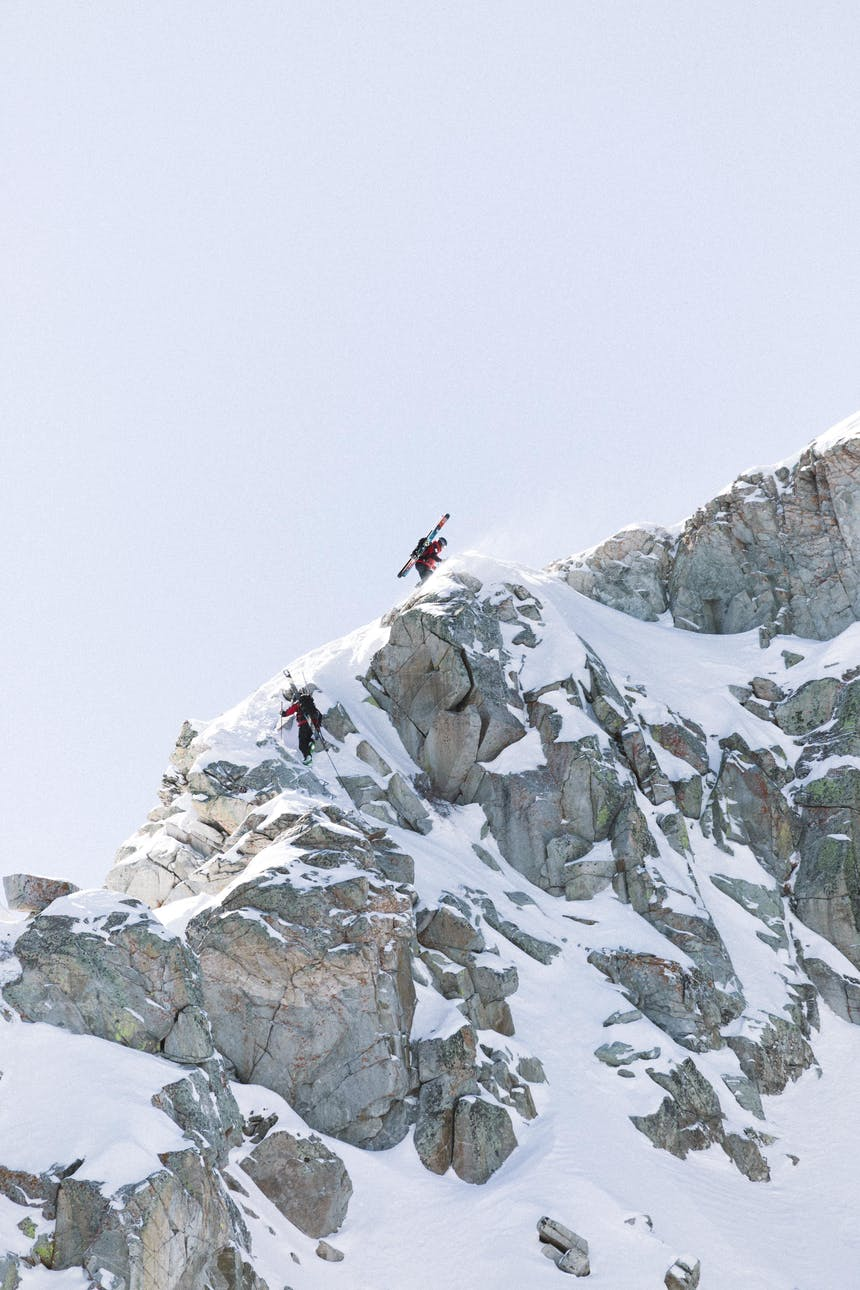 two downhill skiers with their skies strapped to their packs as they climb a rocky mountain peak