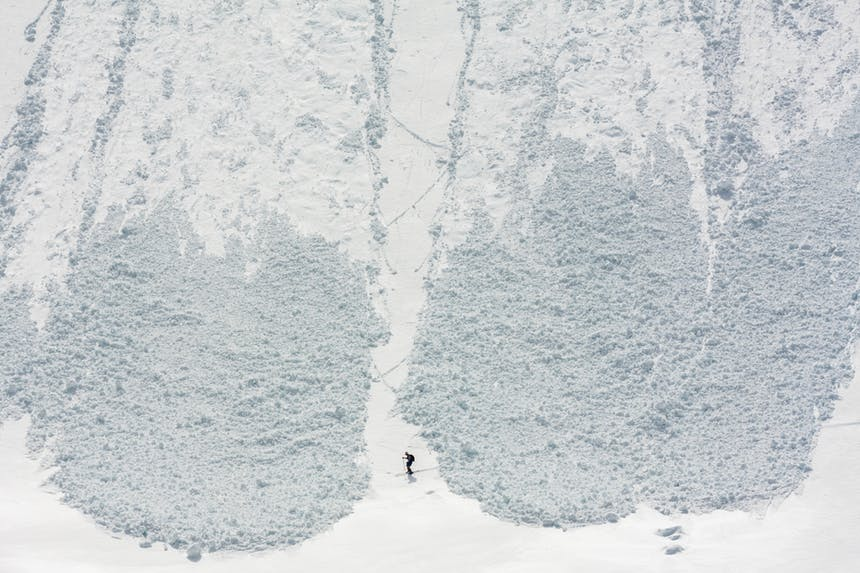 a aerial shot of a skier in the middle of two avalanches coming down the mountain and nearly coming together trapping them