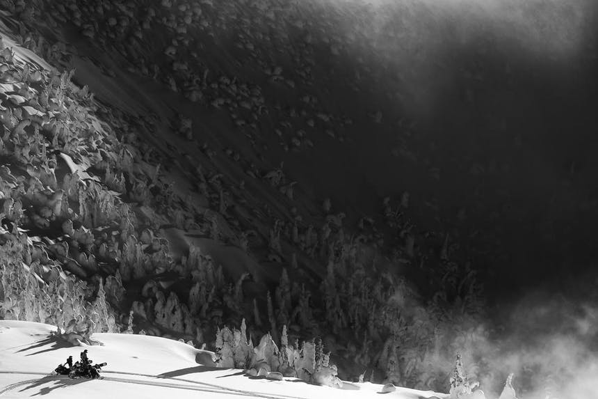 a black and white areal view of two snowmobilers looking off over the rolling snow covered mountains