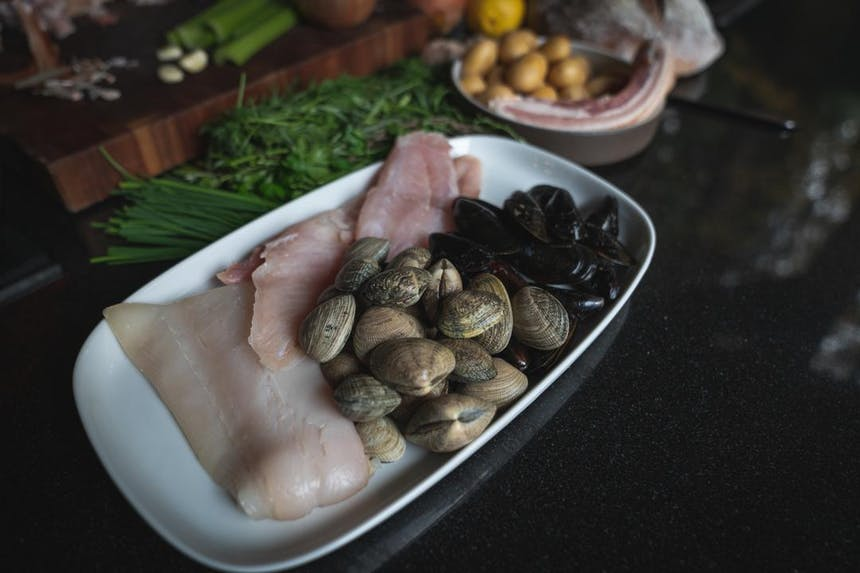 plated seafood, clams, oysters and white fish, next to tarragon and chives on a dark countertop